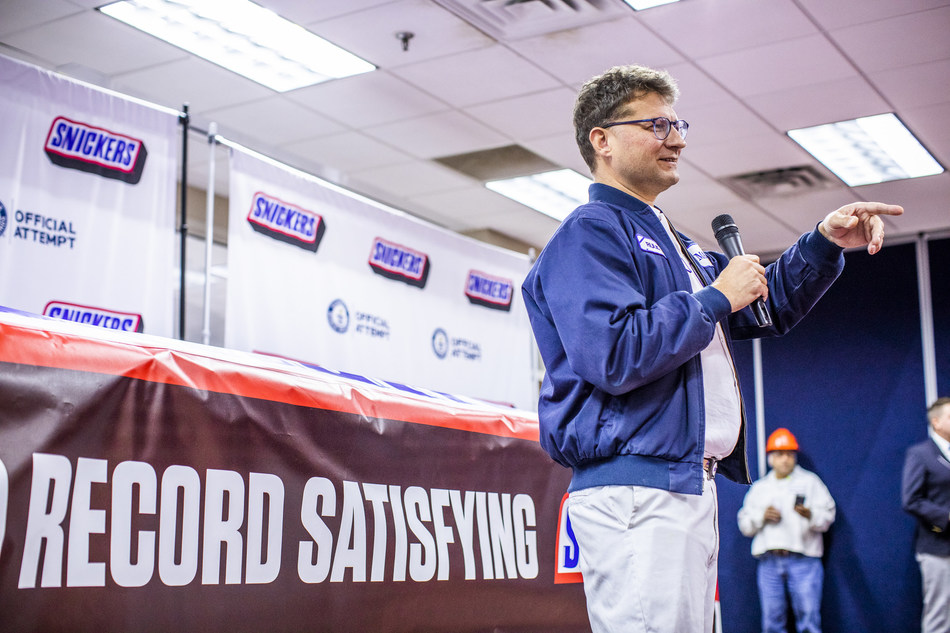 Mars Wrigley representative Ruud Engbers unveils the largest SNICKERS bar ever created Thursday, Jan. 16, 2020, in Waco, Texas. The more than two tons chocolate nut bar was made using a 1200 pound combination of caramel, nougat and peanuts, and 3500 pounds of chocolate.  (Drew Anthony Smith/AP Images for SNICKERS)
