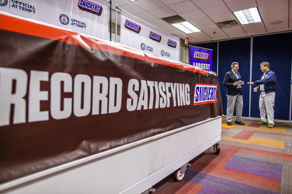 SNICKERS breaks the Guinness World Record title for largest chocolate nut bar on Thursday, Jan. 16, 2020, in Waco, Texas. The more than two tons candy bar was made using a 1200 pound combination of caramel, nougat and peanuts, and 3500 pounds of chocolate.  (Drew Anthony Smith/AP Images for SNICKERS)