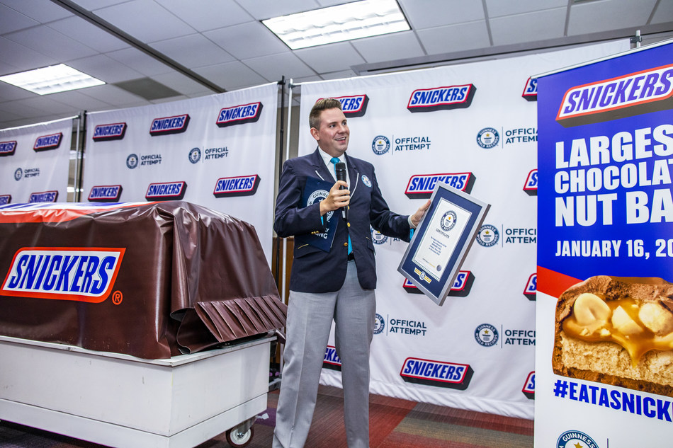 Guinness World Record adjudicator Michael Empric presents title certification for the largest chocolate nut bar ever created Thursday, Jan. 16, 2020, in Waco, Texas. The more than two tons SNICKERS bar was made using a 1200 pound combination of caramel, nougat and peanuts, and  3500 pounds of chocolate.  (Drew Anthony Smith/AP Images for SNICKERS)