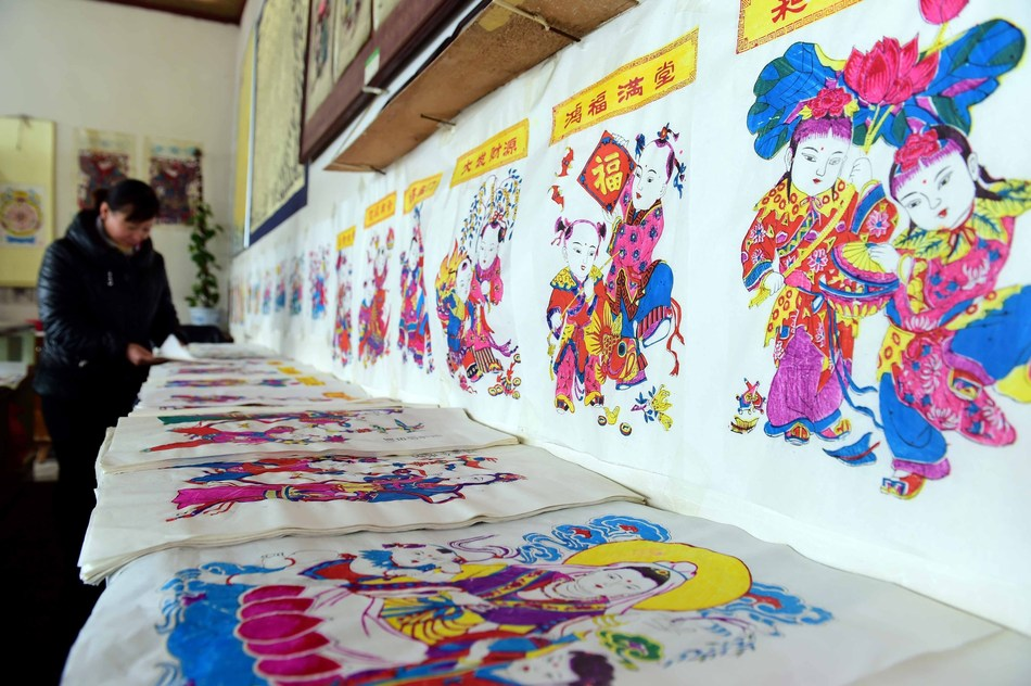 As the New Year approaches, the workshops of the Yangjiabu Woodblock New Year Paintings are getting busy supplying the festival market. In the photo, a worker is sorting out the newly printed New Year paintings. (PRNewsfoto/Weifang Release)