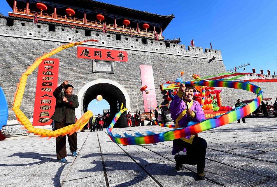 Inheritors of intangible cultural heritages are performing the Chinese yo-yo in the temple fair held in Qingzhou Ancient City Tourist Area in Weifang, which attracts many tourists for Spring Festival celebrations. (PRNewsfoto/Weifang Release)