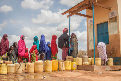 Young girls and women stand in line to get water for their families from a Helping Hand for Relief and Development Borehole Water Project in Anole County, Tana River, Madogo, Kenya. (PRNewsfoto/Helping Hand for Relief and Dev)