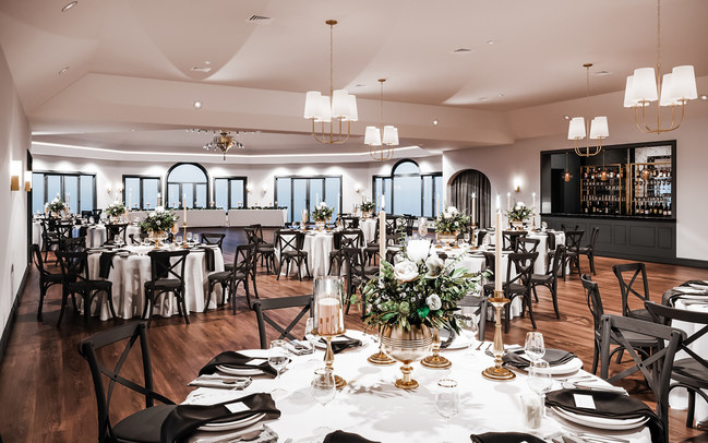 Couples who book Granite Rose by Wedgewood Weddings can enjoy cross-back chairs, modern black accents, contemporary chandeliers, and elegant wood flooring.