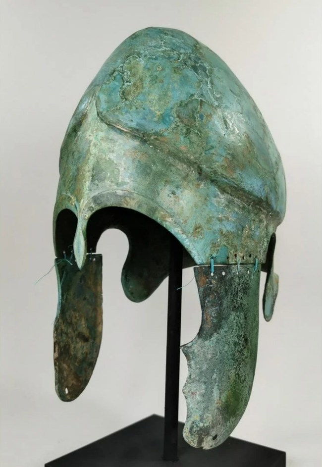 Rare Greek Hoplite Chalcidian helmet with cheek-guards, circa 400 B.C., mounted on included custom-made stand. Ex collection of London art expert and obtained from old British collection. Estimate: $19,500-$32,500