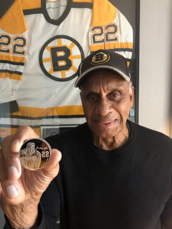 NHL trailblazer Willie O'Ree holds the Royal Canadian Mint's Black History Month coin bearing his engraved portrait. Fredericton-born O'Ree was the first black person to play in the NHL. (CNW Group/Royal Canadian Mint)