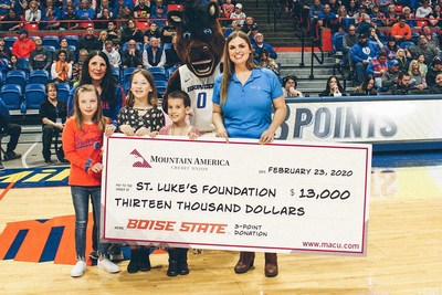 Angela Phillips of Mountain America presents to Sherry Iverson, St. Luke's Children's Director of Community Education alongside Buster Bronco at Boise State University during the February 23 game.