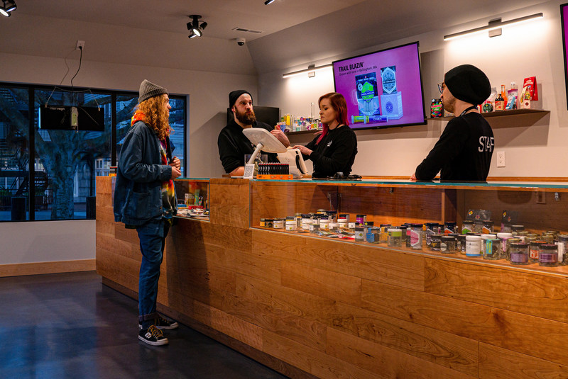 Customer making a purchase at Lux Pot Shop's newest location in Seattle's Fremont neighborhood