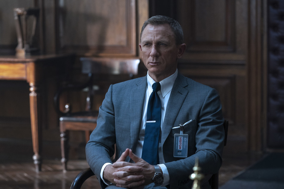 PHOTO CAPTION: B25_11846_RCJames Bond (Daniel Craig) inNO TIME TO DIE,an EON Productions and Metro Goldwyn Mayer Studios film Credit: Nicola Dove© 2020 DANJAQ, LLC AND MGM. ALL RIGHTS RESERVED.PRODUCT DETAILS: TOM FORD Grey Wool Prince of Wales Check O'Connor Notch Lapel Jacket, O'Connor Tailored Trousers, White Poplin Collared Shirt, Dark Blue Diagonal Silk Tie and Off White Silk Pocket Square