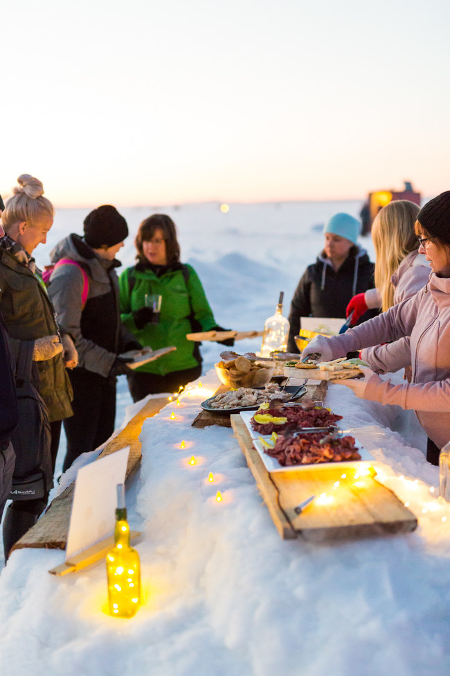 """A 2019 SHiFT learning experience: Aqua Splash, one of Sylvan Lake's most popular summer activities, demonstrated how to transform a product into a winter experience. The """"Evolution of Ice"""" took participants through different stations on the lake including ice fishing, sampling local culinary delights, riding an ice carousel, and trading stories by the fire over a cup of fish broth. (CNW Group/Travel Alberta)"""