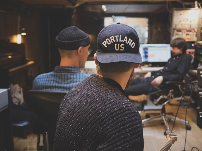 Musicians in a recording studio. Thanks to new technology, a recording studio isn't required for most recordings. Platforms like Tunedly are replacing the traditional recording studio.