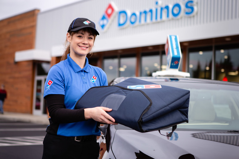Delivery driver standing beside car in front of Domino's store location (CNW Group/Domino's Pizza)