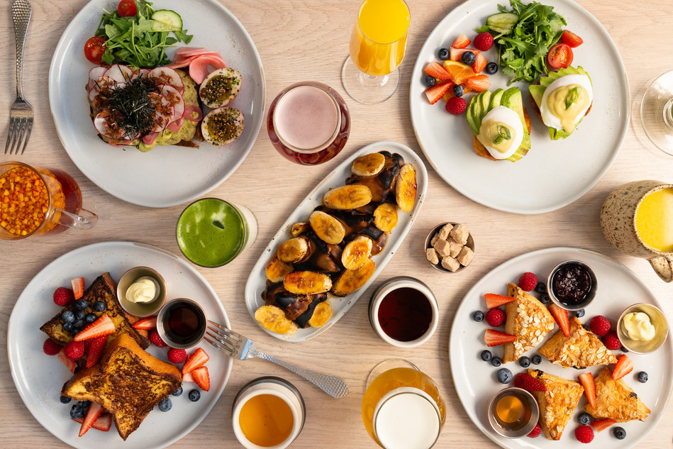 Example breakfast spread including torch-blased banana toast, scone platter, eggs benedict, challah french toast and avocado toast.