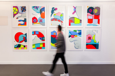 Art investor walks past Blame GamePortfolio, a unique set of 10 prints byKawswhich has been shrouded in mystery since its shadow debut in 2016. (PRNewsfoto/ARTCELS)