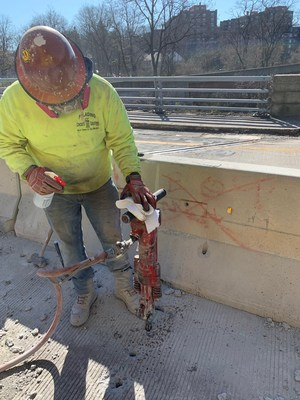 A member of Heavy Construction Laborers Local 60 disinfects a jackhammer before working on the Bronx River Parkway.