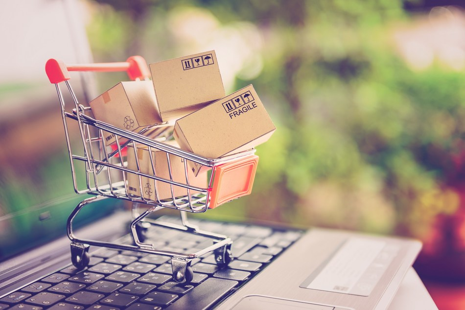 Online shopping and delivery service concept. Paper cartons in a shopping cart on a laptop keyboard, this image implies online shopping that customer order things from retailer sites via the internet. (PRNewsfoto/Research and Markets)