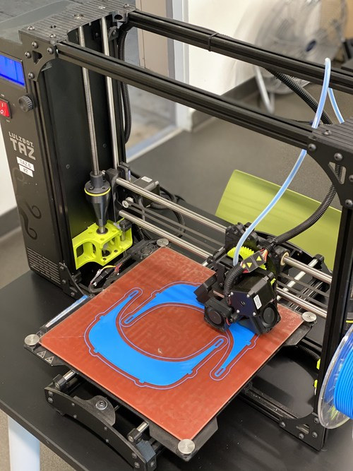 One of Campbell Hall's six 3D printers printing face shields and masks.