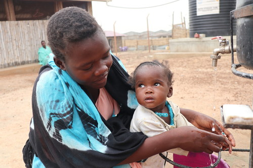 Merlin Benson and her nine-month-old daughter Sarah, wash their hands after a COVID-19 information session at a World Vision South Sudan nutrition centre in Juba. Photo: Scovia Faida Charles Duku (CNW Group/World Vision Canada)