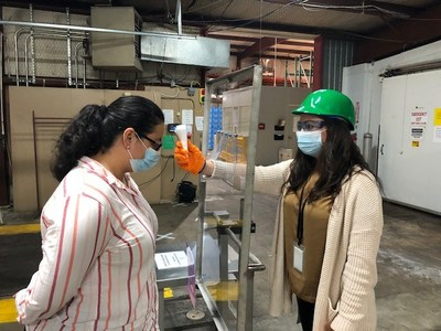 Utilizing infrared non-contact temperature devices, trained testers check the temperatures of associates entering a Perdue Farms facility in Schulenburg, Texas through a protective plexiglass barrier