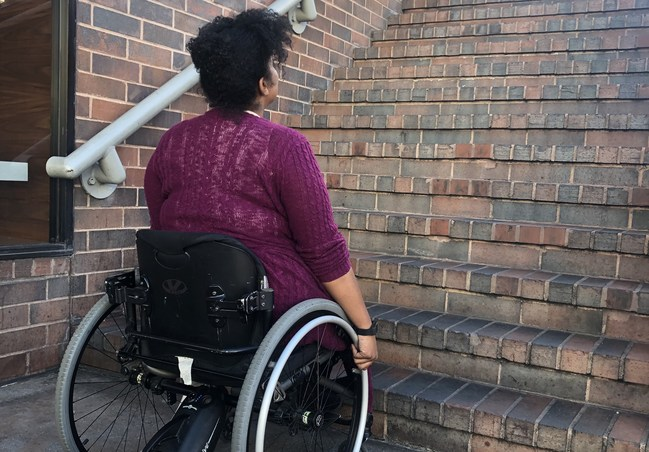 A young African American woman in a wheelchair looking up a flight of stairs