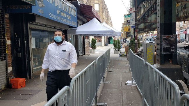 Masbia Volunteer, Mendel Teitelbaum, walking past the social-distancing metal-barriers placed by NYC Office of Emergency Management (OEM) for the swelling breadline in front of Masbia of Boro Park