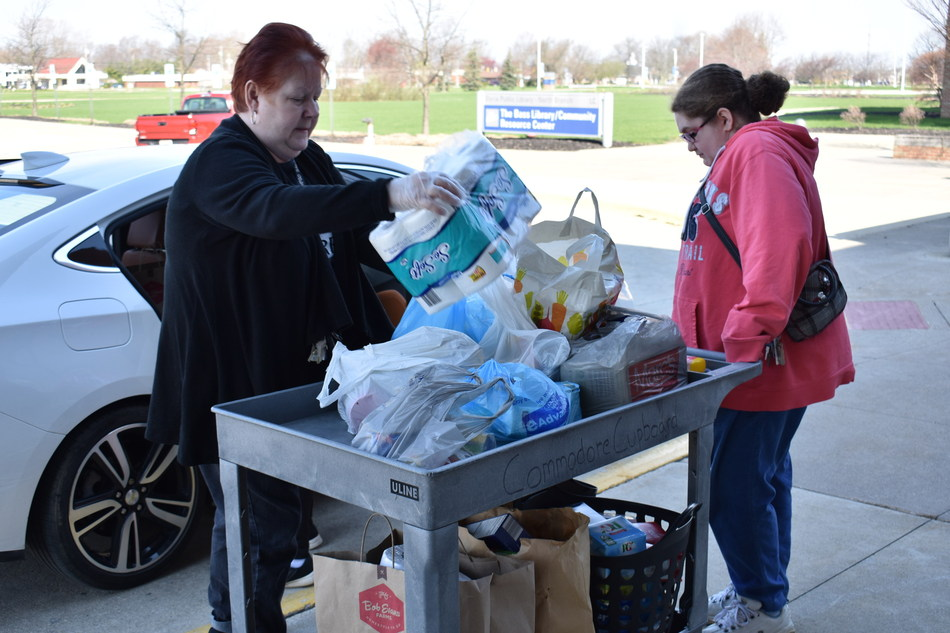 Charlene Dellipoala (left) and Julie Tanner of the LCCC Commodore Cupboard load donated food for the campus food pantry.