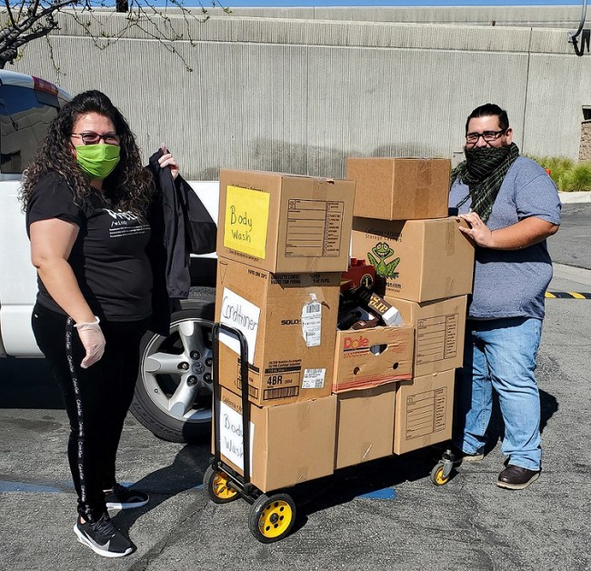 IEHP's Eva Aparicio and Kevinn Porras gather boxes of hygiene products for distribution to local senior living apartments.