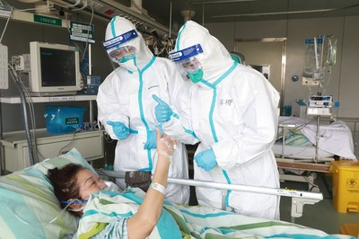 A recovering pneumonia patient gives a thumbs-up to medical workers at Wuhan University's Zhongnan Hospital, on Jan 30, 2020. [Photo by Gao Xiang For China Daily]