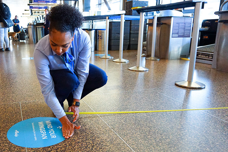 To encourage social distancing, Alaska Airlines is installing floor decals at airports to remind flyers and employees to remain separated by at least six feet.