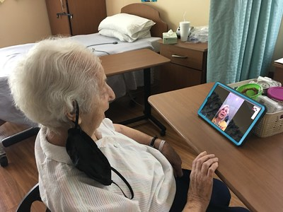 A resident at Palm Garden, one of the first communities to receive iN2L's enhanced tablets through Florida's Project VITAL initiative, calls a loved one using the new video chat application.