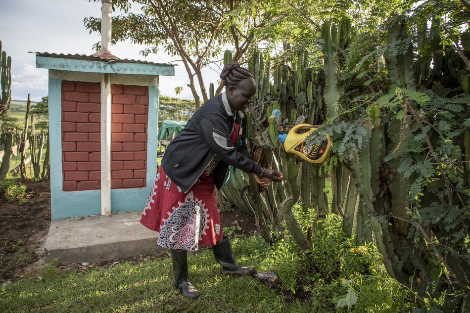 A villager in Kenya demonstrates her handwashing station next to a latrine made of interlocking bricks - a local market-based solution for sustainable sanitation. ©WSSCC/Jason Florio