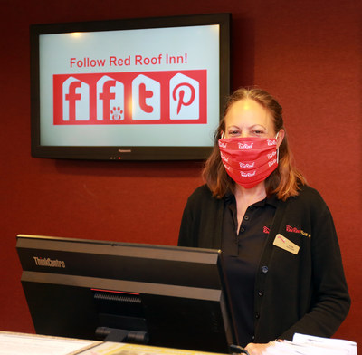 Red Roof front desk representative, Lisa Rowland, greets guests with a smile beneath her cloth face covering, following CDC guidelines and Red Roof RediClean enhanced cleaning protocols.