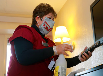 Red Roof housekeeper, Margarita Chavez sanitizes in-room high touchpoints, including TV remotes as part of  Red Roof RediClean which includes rigorous enhanced cleaning protocols that address the new normal and give consumers the confidence they need to hit the road again.
