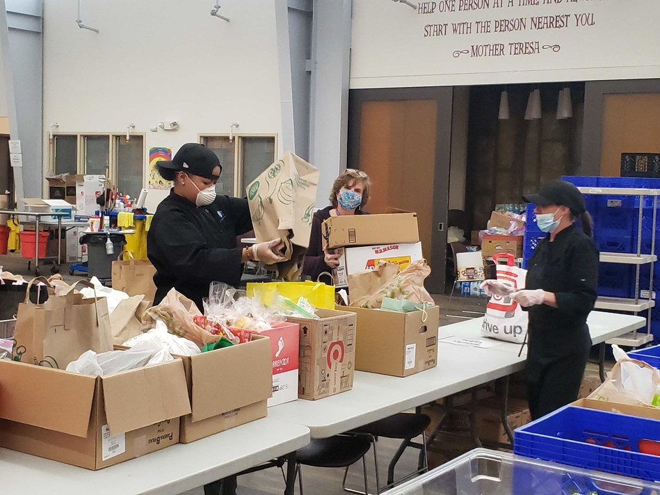 Staff members from Cathedral Kitchen help sort food and supplies for the organization's to-go meal program.