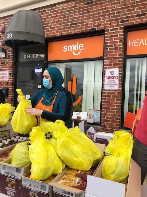 A volunteer helps distribute food packages at SMILE for Charity Food Pantry in Passaic County.