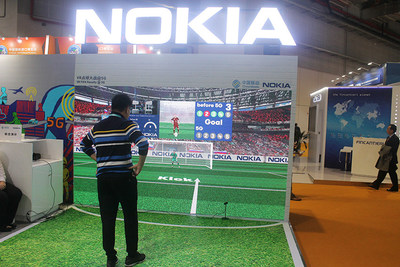 A visitor experiences an interactive football shooting game supported by 5G technology at Nokia's exhibition stand during the First China International Import Expo on Nov. 8, 2018.