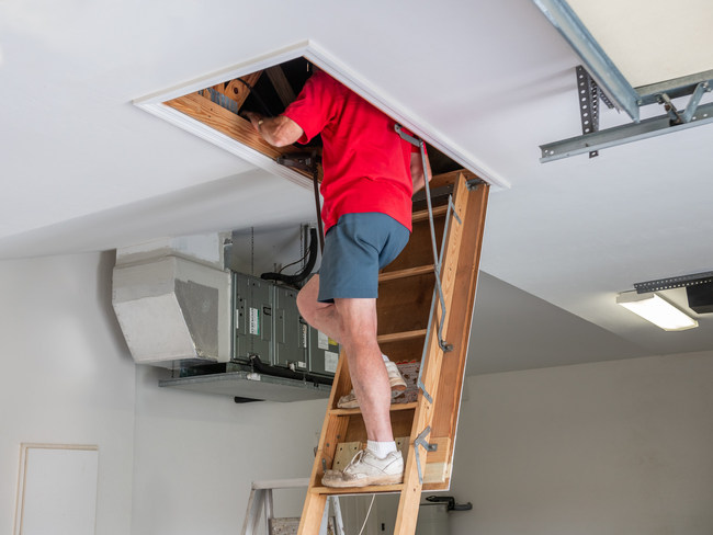 Man inspecting garage attic. Male homeowner climbing wooden pull-down attic ladder. By The Toidi