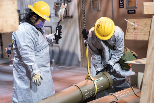 Two operators place one of the last overpacked 8-inch projectiles containing the GB nerve agent into a tray to begin the destruction process at the Blue Grass Chemical Agent-Destruction Pilot Plant in Kentucky. The final 8-inch projectile of GB was destroyed on May 11, marking the complete elimination of an entire type of chemical weapon.