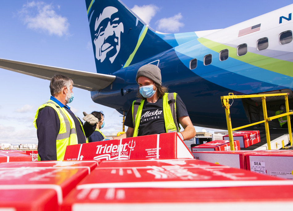 Alaska Air Cargo employees begin to unload 9,000 pounds of Copper River salmon, part of the first shipment to arrive in Seattle.
