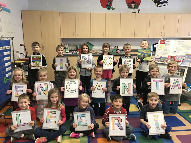 """Pella Christian students are holding up posters that spell out """"We love to read!"""" in Spanish."""