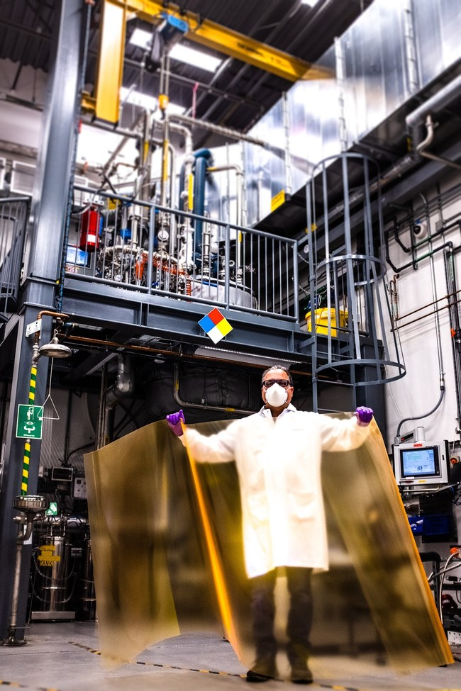 In the foreground, Nanosys Facilities and Equipment Manager presents a sheet of UbiGro® greenhouse film that uses fluorescent quantum dots to help plants get more from the sun. Behind him stands an over 2,000 L quantum dot production reactor.