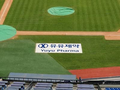 Logotipo de Yuyu Pharma a lo largo de la línea de primera base en el Estadio de Béisbol de Jamsil, en Seúl