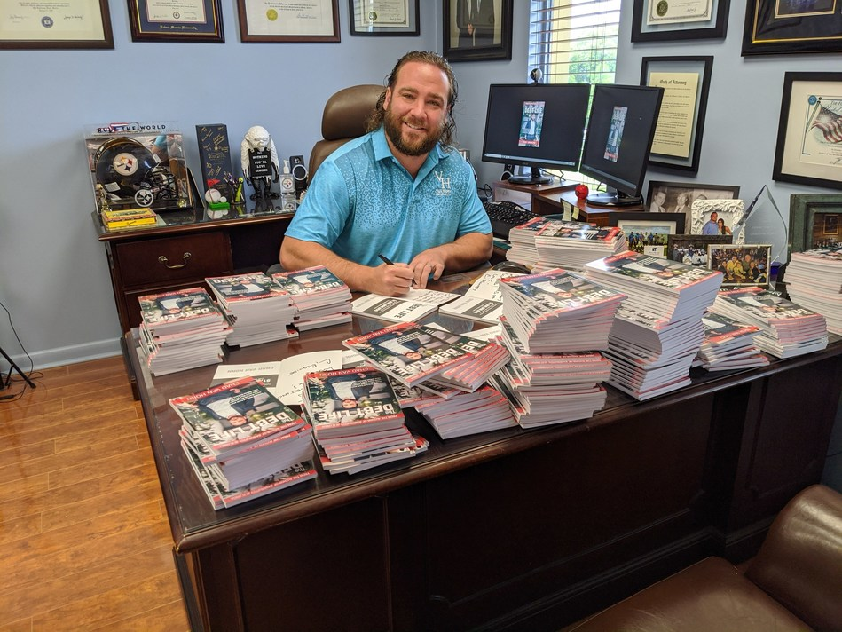 """Bankruptcy attorney Chad Van Horn signs his new book titled """"The Debt Life,"""" a compilation of true stories that illustrate tactics to lift the burden of overwhelming debt. """"The Debt Life"""" is available at www.tinyurl.com/DebtLifePaperback."""