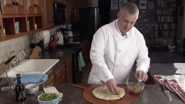 American Flatbread owner, Brad Sterl accessorizing a homemade pizza.
