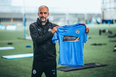 Manchester City manager Pep Guardiola shows off matchday shirt for Premier League return.