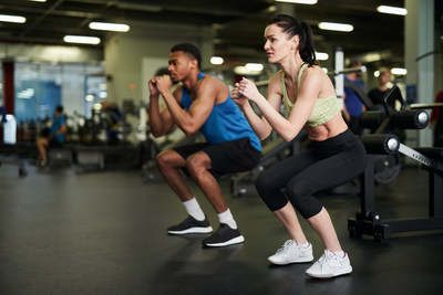 A couple working out in a gym 1-2 metres apart.