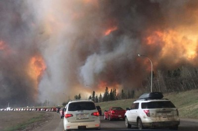Residents evacuating while wildfire advances along evacuation route.