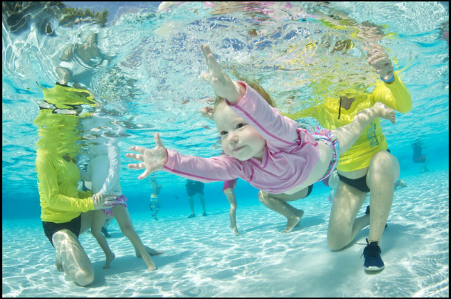 A young swimmer works on opening her eyes underwater during the World's Largest Swimming Lesson. The American Academy of Pediatrics now recommends swim lessons as a layer of protection against drowning that can begin as early as age 1. Parents can work to introduce good water safety habits and start building swim readiness skills at home.