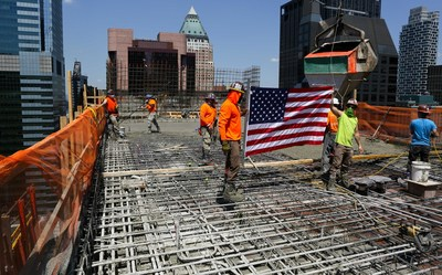 """The construction team at the site of the future Hard Rock Hotel New York hoists the U.S. flag high above Times Square to commemorate the """"topping out"""" of the fundamental framework of Hard Rock Hotel New York's 35th floor terrace. PHOTO CREDIT: Lori Berkowitz"""