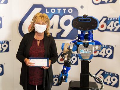 Guylaine Desjardins, la gagnante, et SARA, le robot conçu, coordonné et contrôlé par le club étudiant Walking Machine de l'ÉTS (Groupe CNW/Loto-Québec)