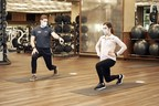 Picture of a personal trainer and woman exercising while they're wearing masks